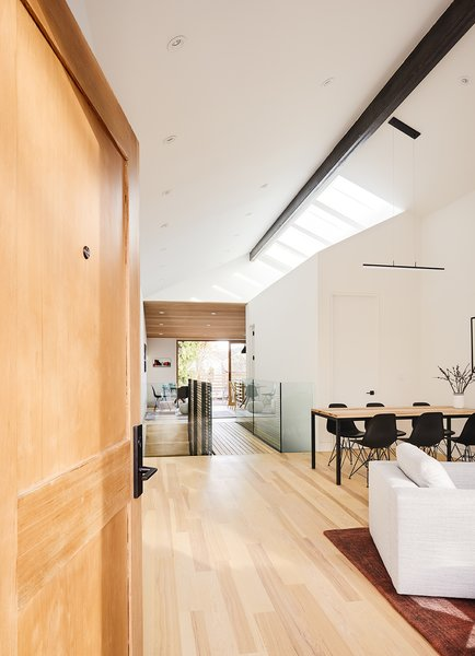 Above an enclosed volume containing a powder room and guest room, a quartet of skylights brightens the living and dining area. A Sonneman Stiletto pendant offers extra light.