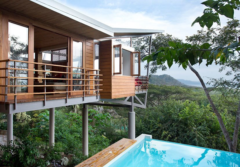 Outdoor, Trees, and Infinity Pools, Tubs, Shower The Floating House floats above the jungle canopy of Costa Rica and was designed by architect Benjamin Garcia Saxe. It's a short walk to the beach and offers elegance that's rooted in nature and simplicity. The structure is made up of three pods that are connected by elevated, outdoor bridges and walkways. Teak flooring and furniture add natural warmth to the main living areas, which are connected to two upstairs bedrooms and an open-air spa bathroom via a 24-meter walkway. The home also features a lounge framed by Concertina floor-to-ceiling glass doors with expansive views of the ocean and jungle.  Photo 5 of 11 in 10 Modernist Beach Home Rentals to  Escape to This Summer