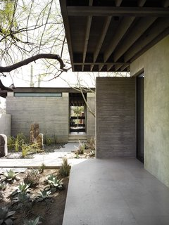 The Phoenix home of designers and builders Sarah Swartz Wessel and Ethan Wessel sits amid desert-friendly trees and plants. The couple bought the property in 1998 and worked on the house for a decade. Juxtaposed with limestone floors, wood-beamed ceilings, and walls of hand-troweled plaster and board-formed concrete, glass is strategically placed throughout the 4,000-square-foot expanse to frame slivers of landscape and sky or open wide to reveal gardens of various sizes, which the couple also designed.