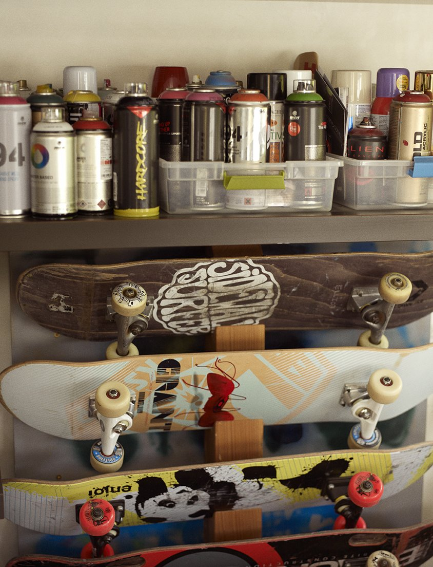 Concrete Counter, Den Room Type, Chair, Ceiling Lighting, Garden, Gardens, Flowers, Concrete Floor, Vegetables, and Storage Room In the music room, skateboards are stored below spray paints the family and friends use to decorate the skate bowl.  Wessel Residence