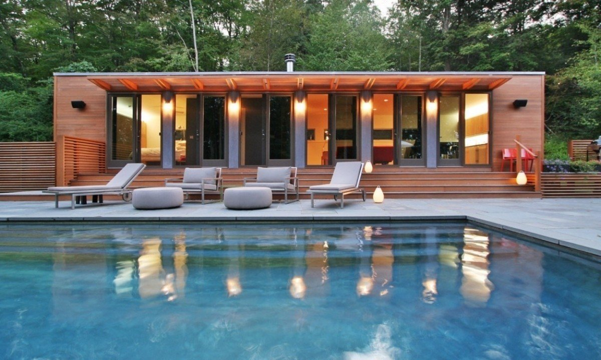 This pool house in Connecticut was fashioned from two shipping containers, bedecked in well-lit cedar, which contrasts beautifully with the blue of the water. Tagged: Outdoor, Swimming Pools, Tubs, Shower, Stone Patio, Porch, Deck, and Trees.  Photo 7 of 10 in 10 Sunny Poolside Prefabs