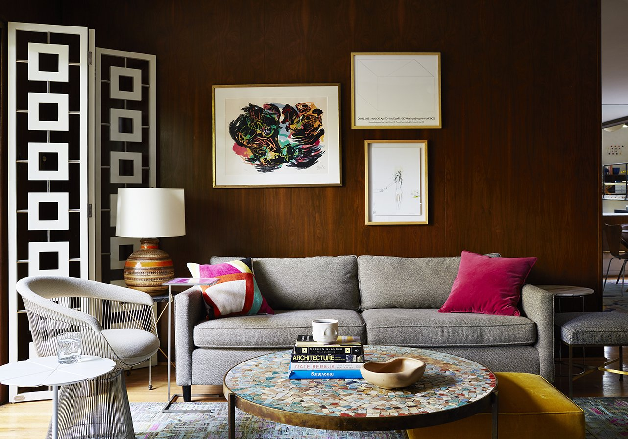 Living Room, Ottomans, Chair, Coffee Tables, Sofa, Lamps, Table Lighting, End Tables, Light Hardwood Floor, and Rug Floor A Petal end table by Richard Schultz is paired with a Platner armchair. These classics mingle with newer items, such as a Desmond room divider by Jonathan Adler and a sofa by Mitchell Gold + Bob Williams.  Photo 11 of 13 in How to Update a Midcentury Modern Gem