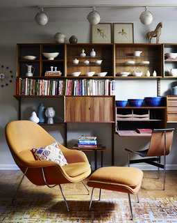 Illuminated by track lighting, a teak wall unit by Poul Cadovius showcases pottery by Eva Zeisel and Paul McCobb, among others. The desk seat is a T chair by William Katavolos, Ross Littell, and Douglas Kelley; the Womb chair is by Eero Saarinen for Knoll.