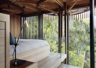 Lofted amid eucalyptus and oak trees, Graham Paarman's house in South Africa is a glassed-in, steel-frame structure with a veil of vertical slats. Excluding outdoor areas, it measures about 720 square feet. Half-round bays project to form a balcony, a pergola, a dining alcove, and a bathroom.