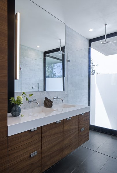 Silestone counters, walnut cabinetry, and Refin floor tiles accent the master bathroom. The Axor Uno faucets are from Hansgrohe, the Alinea vanity light is from Aamsco, and the shower head is by Jaclo.