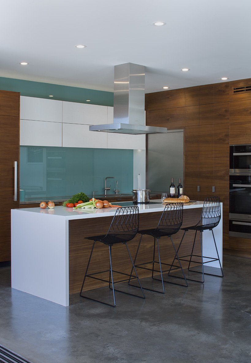 Kitchen, Range Hood, Wood Cabinet, Cooktops, and White Cabinet In the kitchen, a blue glass backsplash evokes the designers' native Iceland. The  Bend Goods stools are from YLiving.  Photo 4 of 12 in A Southern Californian Prefab Is Paradise For the Whole Family