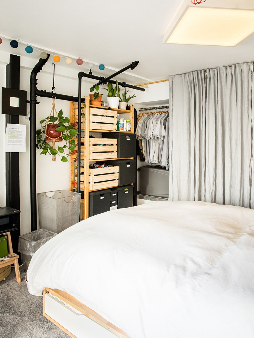 Bedroom, Wardrobe, Ceiling Lighting, Storage, Bed, and Carpet Floor The custom overhead light is a pine box covered in linen, which diffuses  the LEDs inside. A gray linen curtain conceals his tools.  Max's Apartment from Devising Clever Solutions For a Small San Francisco Loft