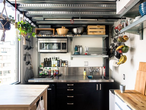 "The kitchen, located behind the stairs and underneath Max's  bedroom, is all electric, with two  burners, a rice cooker, a slow cooker, and a toaster oven. Max added industrial shelving and  a butcher block. ""Vertical storage,"" he notes, ""is very important."""