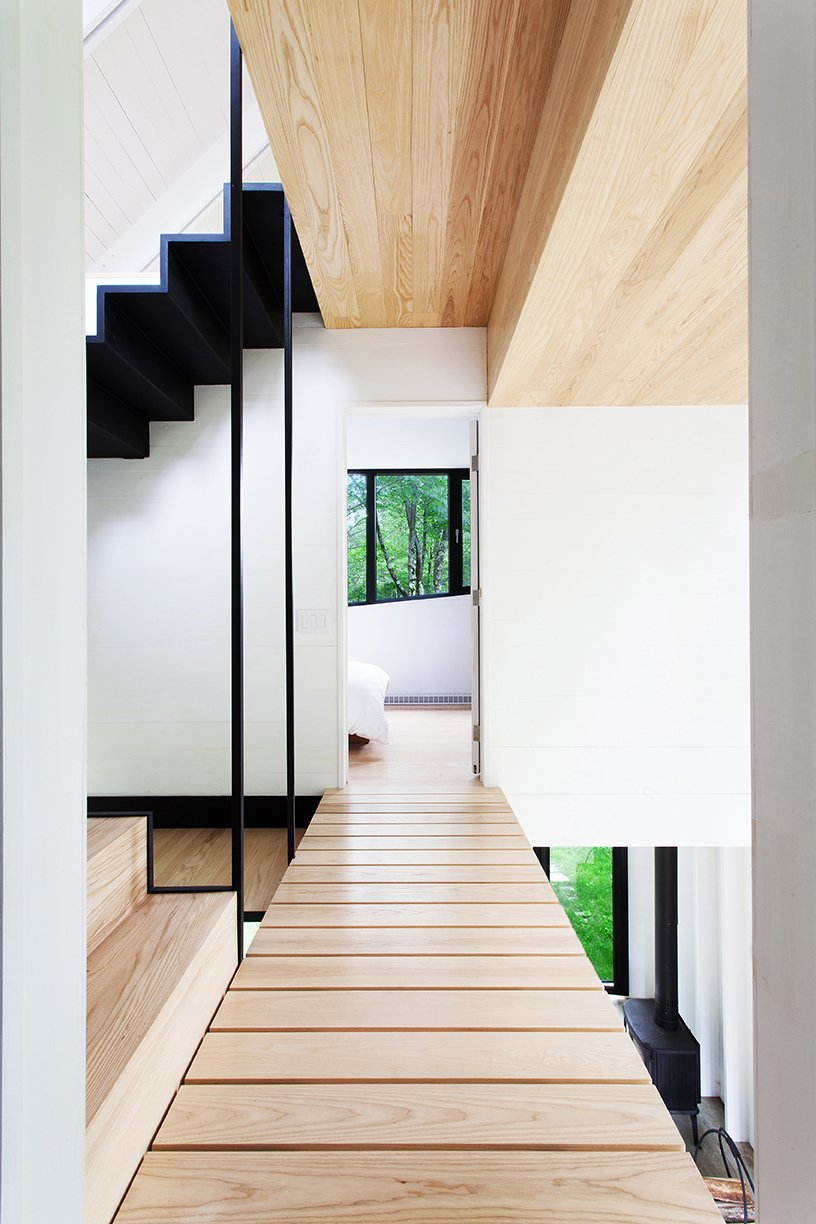 Hallway and Light Hardwood Floor Architects Marie-Claude Hamelin and Loukas Yiacouvakis connected the home's three levels in dramatic fashion. Ash treads float on a steel stringer from the ground floor to the mezzanine.  Photo 6 of 11 in Growing Upward and Outward, a Cabin Expansion Mirrors the Trees