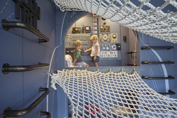 In the cockpit of their imaginary rocket ship, the kids tinker with a dashboard of dials, levers, and knobs assembled by artist Christophe Gauspohl.