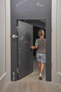 In certain places, the scale of the home is adjusted for children. A standard door, covered in chalk-board paint, has a 48-inch-tall door set inside it.