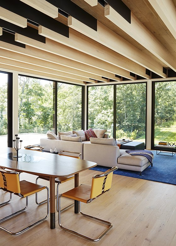 Living Room, Sectional, Sofa, Coffee Tables, Table, Light Hardwood Floor, and Rug Floor In the dining area, a custom table by interior designer Elizabeth Bolognino is surrounded by Spoleto chairs by Knoll.  Photo 5 of 11 in A Family Retreat in the Hamptons Bridles Wind, Water, and Light