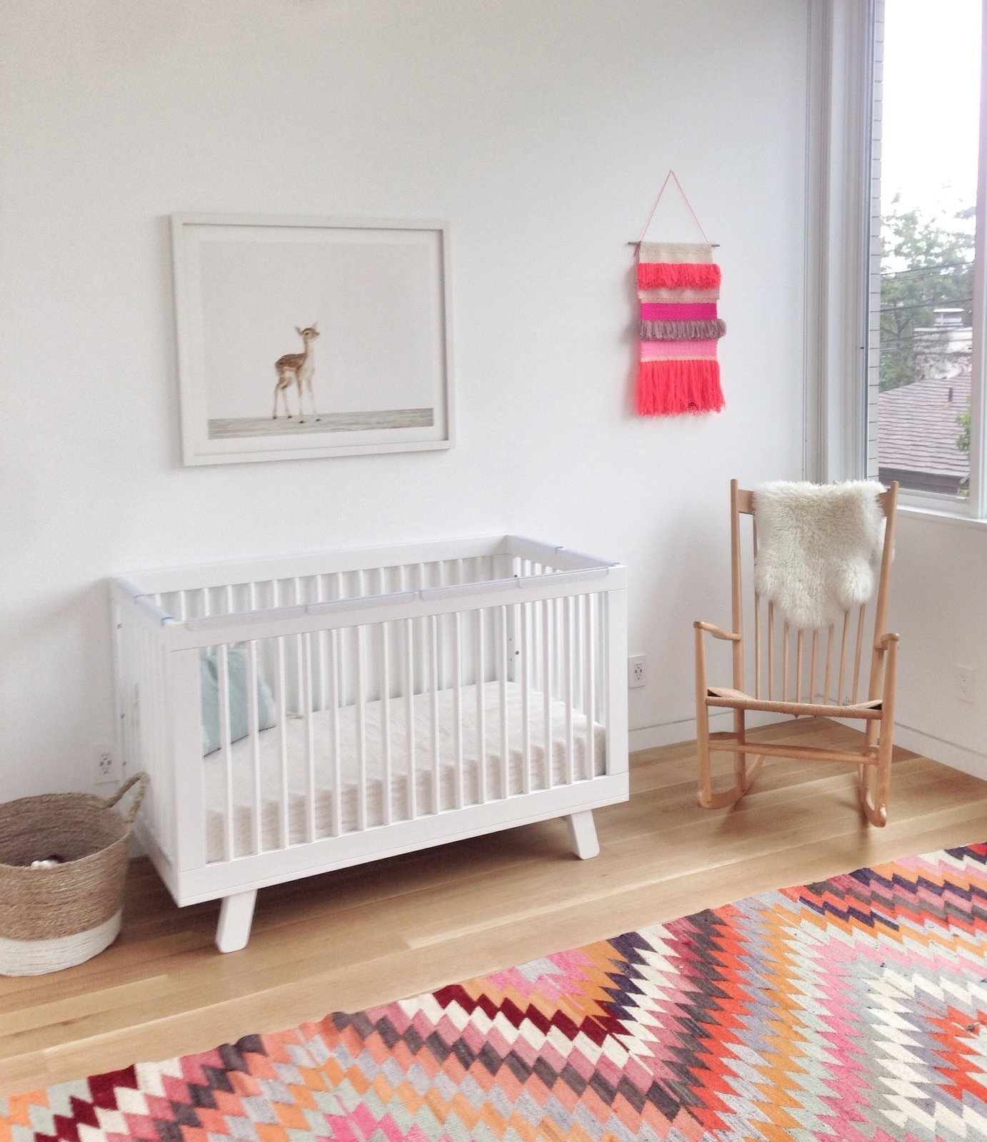 Kids Room, Bed, Light Hardwood Floor, and Bedroom Room Type The resident's daughter, Clara, has a Hudson crib by Babyletto, a vintage J16 rocker by Hans Wegner, and a vintage rug in her bedroom.  Best Photos