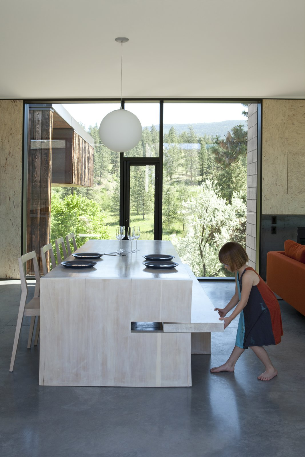 Dining Room, Chair, Concrete Floor, Pendant Lighting, and Table A custom table designed by Jones features a pull-out bench on one side and 1C dining chairs by Room B on the other; the Globo pendant is by Viso.  Photo 6 of 11 in A Hilltop Home in British Columbia That Seems to Grow Out of a Park
