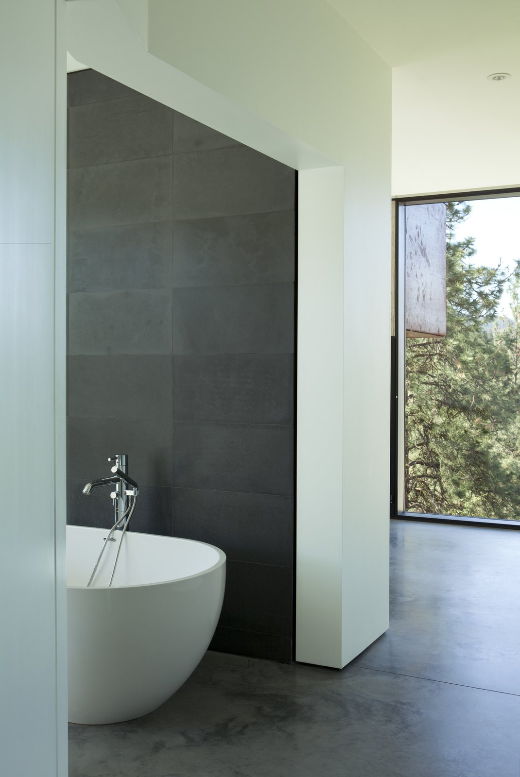 Bath Room, Concrete Floor, Freestanding Tub, and Concrete Counter The bathtub is Aquabagno by Aquabrass.  Friesen-Wong Residence from This Hilltop Home in British Columbia Seems to Grow Out of a Park