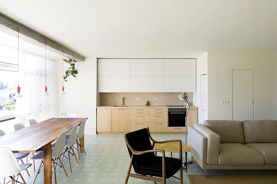 Kitchen, White Cabinet, Wood Cabinet, Wood Counter, Ceramic Tile Floor, Pendant Lighting, Cooktops, Floor Lighting, and Drop In Sink A Nockeby sofa by Ikea, a 45 Chair by Finn Juhl, and an Egg Gold coffee table by Kare are featured in the living room space. - Lisbon, Portugal Dwell Magazine : July / August 2017  Photo 6 of 6 in Lisbon Vision