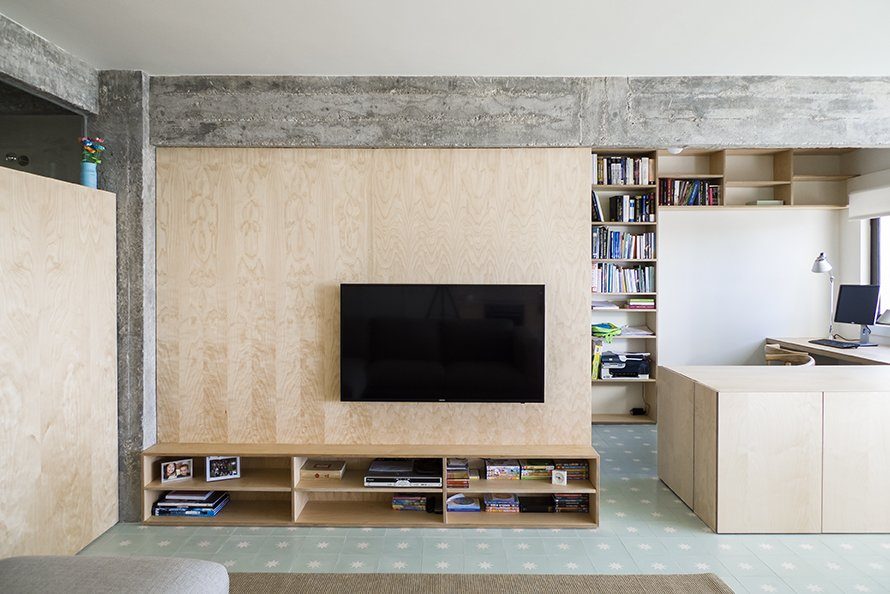 Living, Bookcase, Media Cabinet, Storage, Desk, and Ceramic Tile The living room is defined by a large birch plywood television console, designed by architect, Miguel Marcelino. - Lisbon, Portugal Dwell Magazine : July / August 2017  Best Living Desk Photos from Lisbon Vision