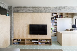 The living room is defined by a large birch plywood television console, designed by architect, Miguel Marcelino. - Lisbon, Portugal Dwell Magazine : July / August 2017
