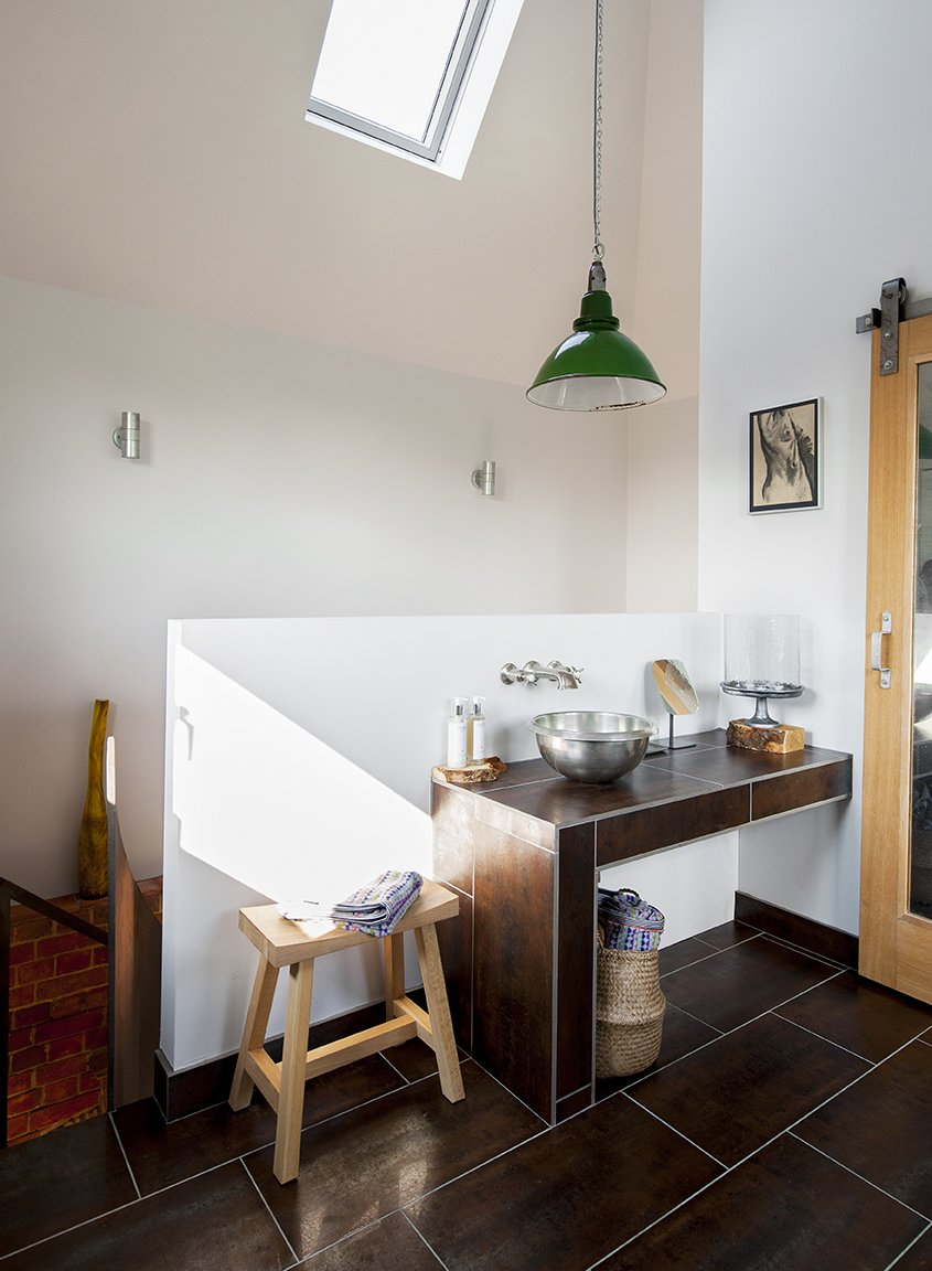 Bath Room, Vessel Sink, and Pendant Lighting The bathroom occupies the highest chamber of the tower. A vintage pendant purchased from Skinflint Design hangs above a copper sink  by William Holland.  Lister Tower from A Refurbished, Victorian-Era Brick Tower in Hampshire