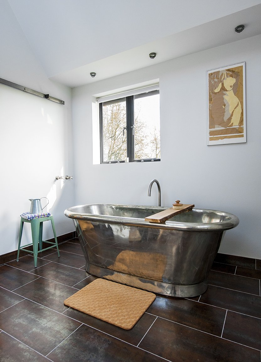 Bath Room, Freestanding Tub, and Ceiling Lighting A freestanding copper tub, also by William Holland, sits exposed in a corner of the bathroom. The matching tile for the vanity and floor is by Marco Polo.  Lister Tower from A Refurbished, Victorian-Era Brick Tower in Hampshire