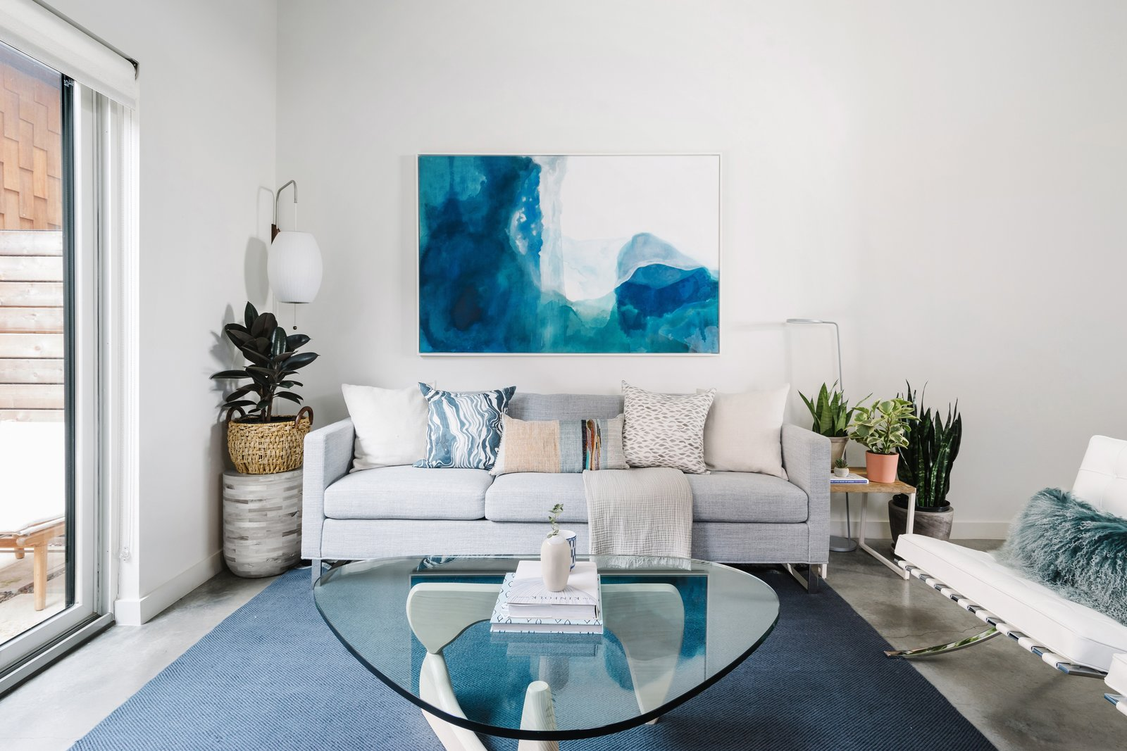 Living Room, Chair, Coffee Tables, End Tables, Sofa, Lamps, Concrete Floor, and Floor Lighting This room was inspired by the owners' love of St. Barts.  St. Barts-Inspired Tilley Row Home from St. Barts-Inspired Accents Create Modern Tranquility in an Austin Tilley Row Home