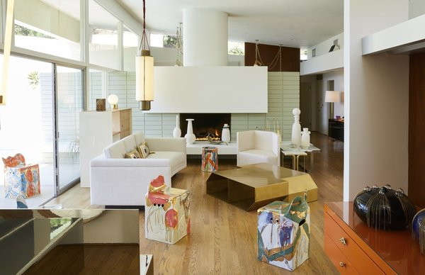 The bright and airy gallery space with a contemporary fireplace, sliding glass doors and a backyard pool serves as the perfect setting for Sanguino's work.