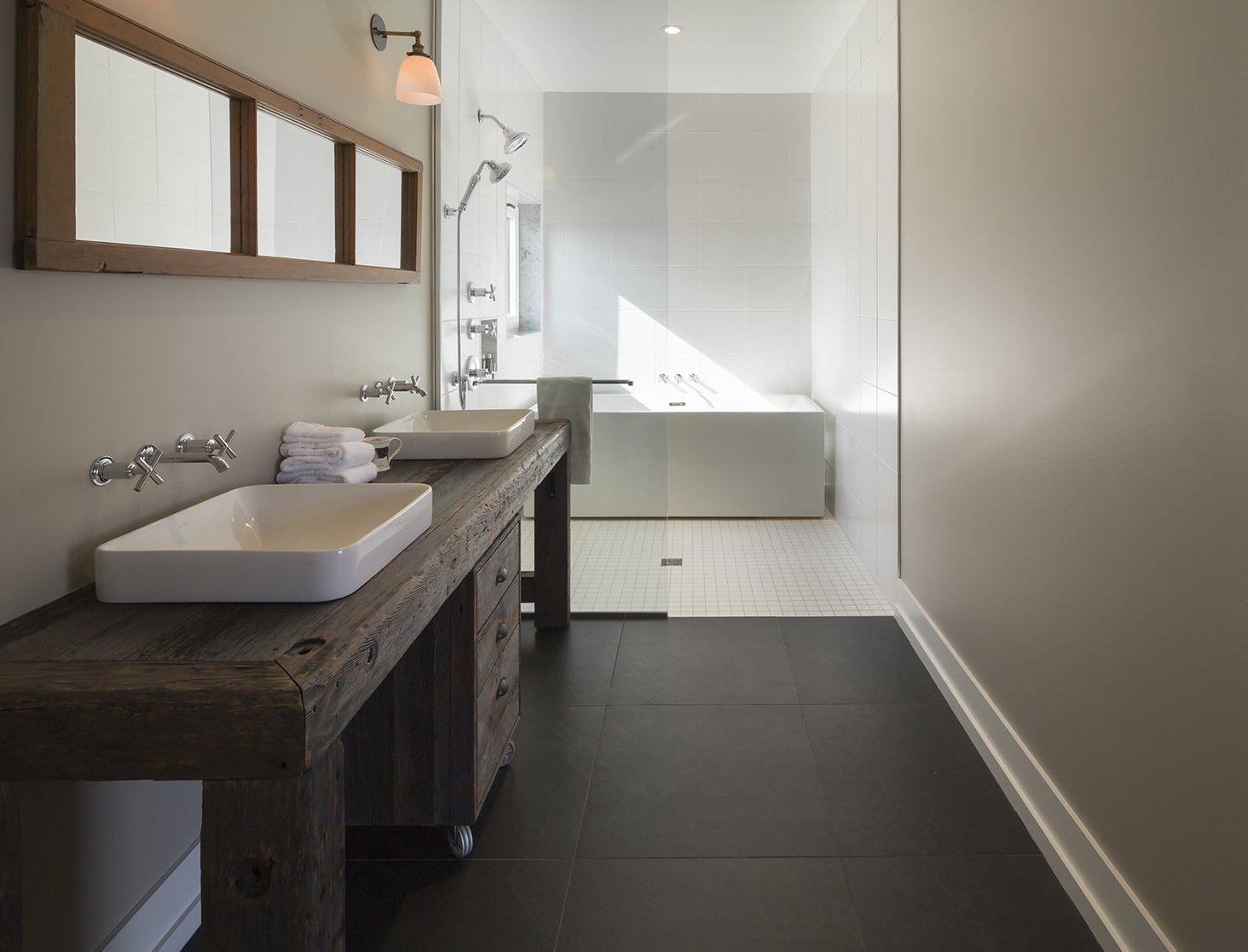 Bath Room, Wood Counter, Open Shower, Freestanding Tub, and Vessel Sink The master bathroom features sinks and fixtures by Kohler. The tub is by Aktuell. - North Hatley, Quebec Dwell Magazine : July / August 2017  Photo 9 of 12 in An Artist and Farmer Work With a Toronto-Based Studio to Build a Barn-Inspired Home