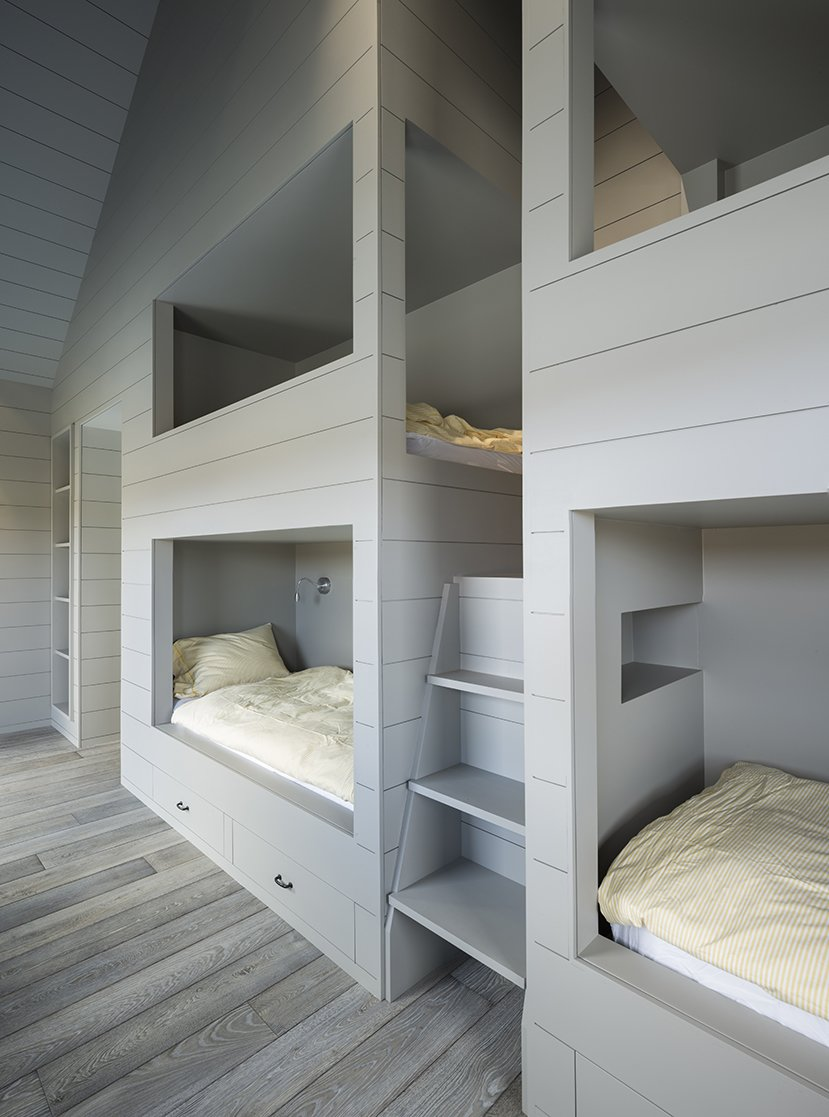 Bedroom, Medium Hardwood Floor, Bunks, Bed, and Storage LAMAS designed a quartet of bunkbeds large enough for adults. - North Hatley, Quebec Dwell Magazine : July / August 2017  Best Photos from An Artist and Farmer Work With a Toronto-Based Studio to Build a Barn-Inspired Home
