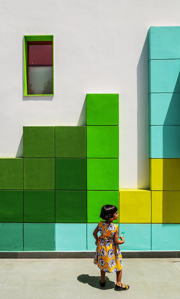 """The facade of the building, which is known as """"The Tetrisception,"""" is decorated with a series of 17.5-inch-square plastered brick cubes, a low-cost design technique.  Photo 2 of 2 in A Dilapidated Home in New Delhi Is Transformed Into a School That Fosters Creativity"""