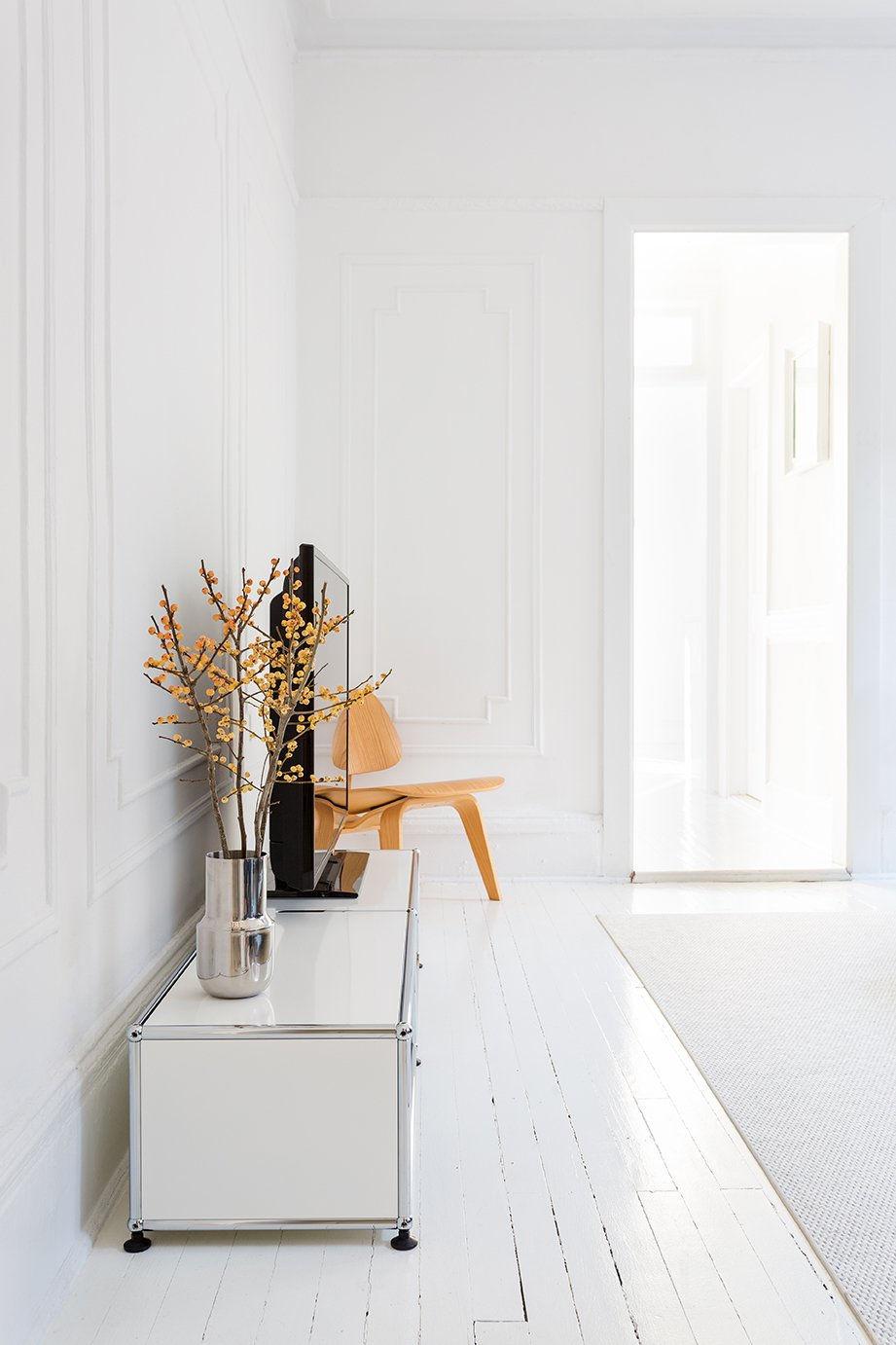 """Living Room, Chair, and Painted Wood Floor """"When everything is painted white, you can really feel the spatial flow and the sectional geometry, which is interesting because it goes from being a rectangle to a square."""" Ed Parker, designer and resident - Brooklyn, New York Dwell Magazine : July / August 2017  Photo 6 of 13 in A Pair of Designers Renovate Their Brooklyn Brownstone With a Bright Monochromatic Palette"""