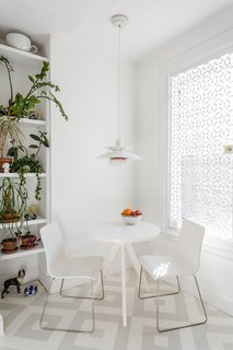 In the kitchen, a PH 50 pendant by Poul Henningsen for Louis Poulsen hangs overhead; the window is covered in a decorative cast-iron metal security grate from King Architectural Metals. The painted patterned floor is by Lillian Heard Studio. - Brooklyn, New York Dwell Magazine : July / August 2017