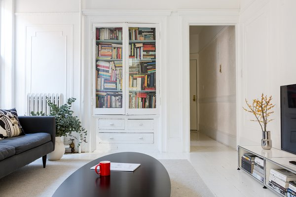 Ed Parker and his wife, Barbara Tutino Parker, use the TV room cabinet to store their overflowing book collection. Though not a library per se, it serves as such for the Brooklyn brownstone.