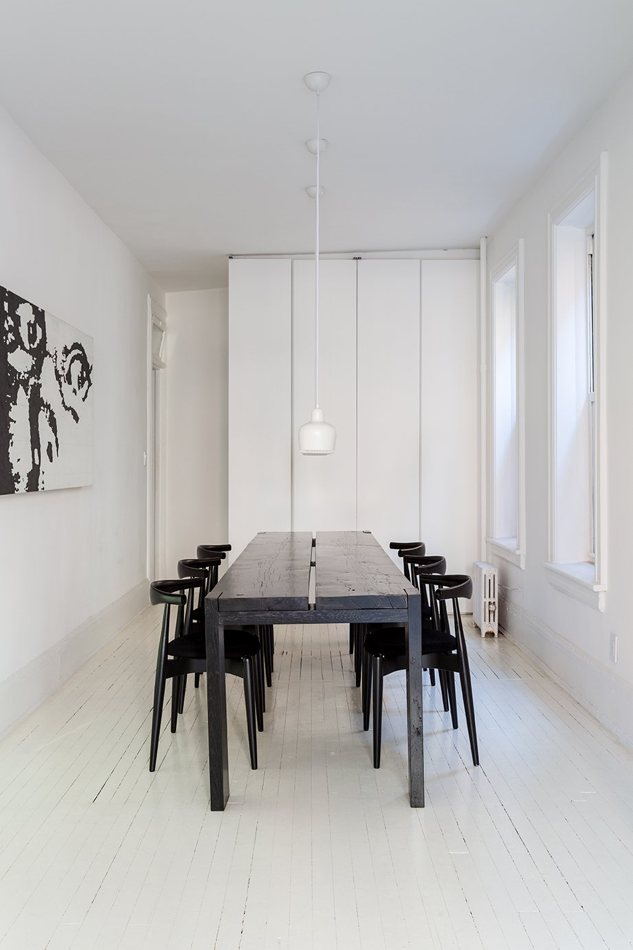 Dining Room, Chair, Table, Pendant Lighting, and Painted Wood Floor Elbow chairs by Hans J. Wegner  for Carl Hansen & Søn surround  a table of the couple's own design. By removing walls in this space, extra storage was possible. The trio of A330S pendants are by Alvar Aalto for Artek. The painting, The Look, is by Ed Parker. - Brooklyn, New York Dwell Magazine : July / August 2017  Photos from A Pair of Designers Renovate Their Brooklyn Brownstone With a Bright Monochromatic Palette