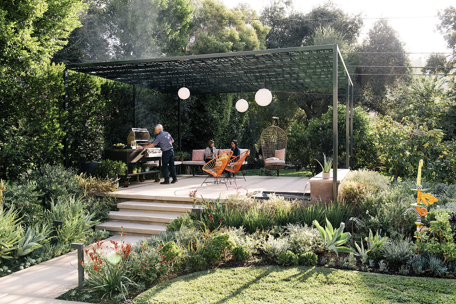 Outdoor, Back Yard, Trees, Shrubs, Flowers, Gardens, Walkways, Large Patio, Porch, Deck, Metal Fences, Wall, Hanging Lighting, and Landscape Lighting Landscape designer Lillian Montalvo swapped disparate plantings for a cohesive plan centered on a pergola. The elevated, covered deck acts like a less constricted gazebo with more air flow.   Photo 10 of 11 in Dwell's Top 10 Outdoor Spaces of 2017 from A Laser-Cut Pergola Completes a Tranquil Garden in L.A. That's Perfect For Entertaining