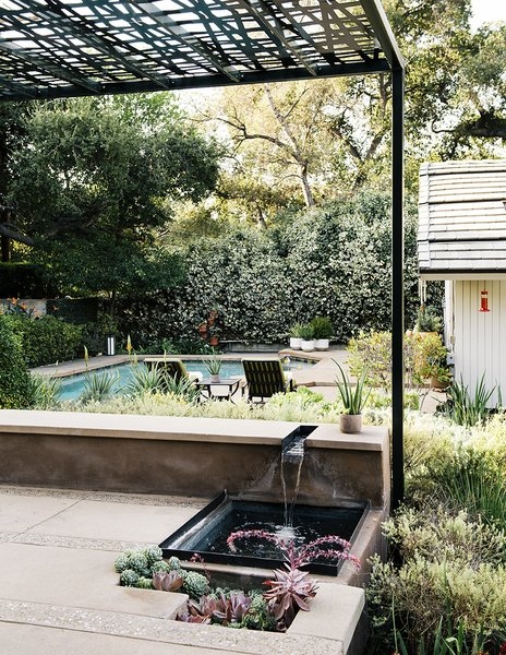 Water recirculates from a bench-level channel into a shallow pool bordered by succulents. Montalvo's longtime landscape contractor Santiago Vasquez worked with her on the hardscaping.
