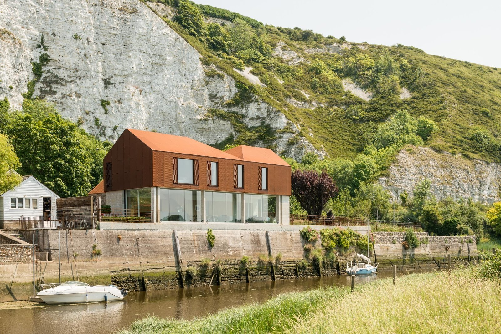 Side Yard, Trees, Grass, Exterior, House Building Type, Metal Roof Material, and Metal Siding Material Perched along the banks of the River Ouse near the historic English town of Lewes is a Cor-Ten steel house with a  Photo 5 of 10 in Dwell's Top 10 Prefabs of 2017 from Explore a Prefabricated House For Sale in England That's Clad With Cor-Ten Steel