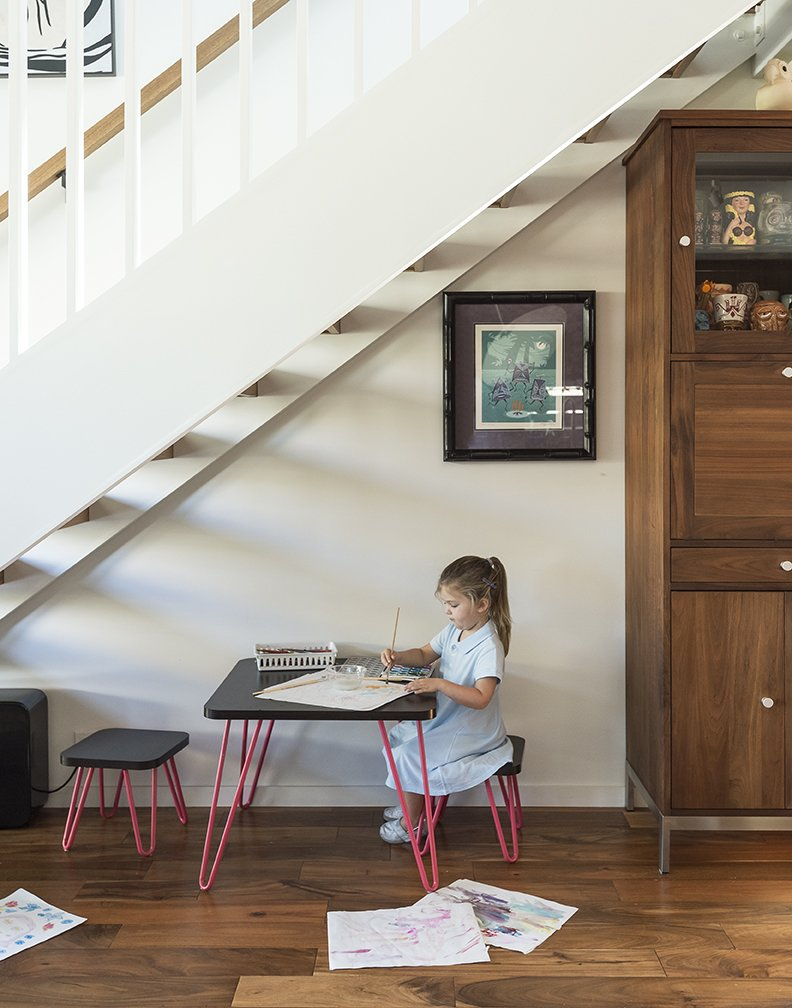 Kids, Medium Hardwood, Chair, Toddler, and Girl TJ and Jay's daughter, Chloe,  colors at an Ameriwood Home table  from AllModern. - Santa Monica, California Dwell Magazine : July / August 2017  Best Kids Toddler Medium Hardwood Photos from A Family's Cramped Bungalow Is Replaced With an Accessible and Affordable Prefab