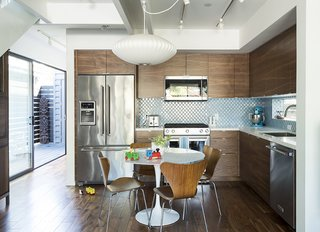 The dining  area features a custom Eero Saarinen table for Knoll and vintage Arne Jacobsen chairs for Fritz Hansen. KitchenAid appliances, IKEA cabinets, and Home Depot tile furnish the kitchen. - Santa Monica, California Dwell Magazine : July / August 2017