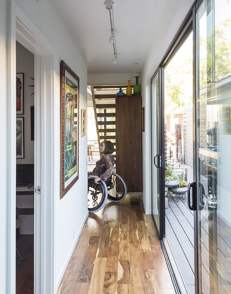 Hallway and Medium Hardwood Floor Ensuring that the house would be accessible for wheelchair users like Marielle Kriesel, who serves on the Santa Monica Disabilities Commission with TJ, guided the design. - Santa Monica, California Dwell Magazine : July / August 2017  Hill-Heiserman House from A Family's Cramped Bungalow Is Replaced With an Accessible and Affordable Prefab