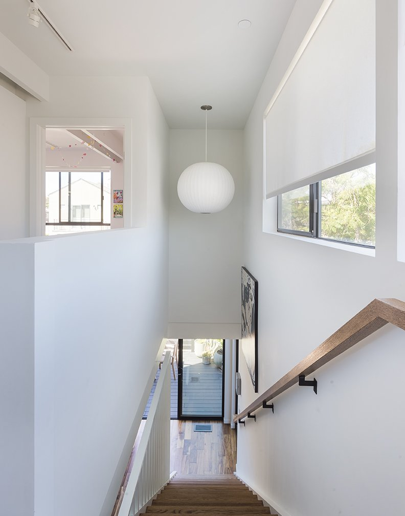 Staircase and Wood Railing A George Nelson Bubble lamp hangs in the stairwell. - Santa Monica, California Dwell Magazine : July / August 2017  Photo 10 of 14 in A Family's Cramped Bungalow Is Replaced With an Accessible and Affordable Prefab
