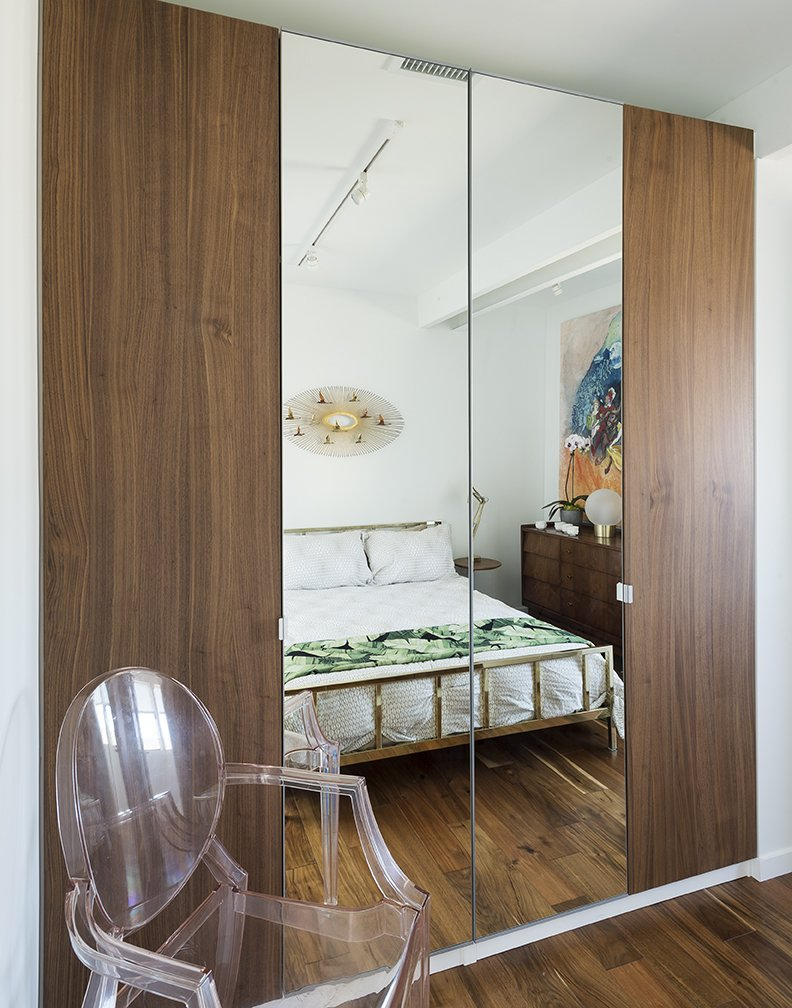 Bedroom, Night Stands, Dresser, Bed, Track Lighting, Ceiling Lighting, Medium Hardwood Floor, and Chair A Curtis Jere sculpture hangs  above a bed from CB2 in the upstairs guestroom. The Louis Ghost chair is by Philippe Starck  for Kartell. - Santa Monica, California Dwell Magazine : July / August 2017  Photo 11 of 14 in A Family's Cramped Bungalow Is Replaced With an Accessible and Affordable Prefab