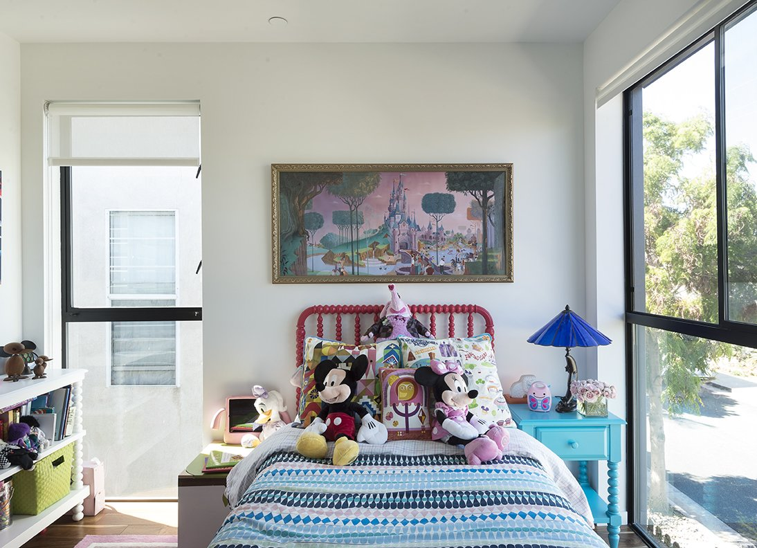 Kids, Bed, Bedroom, Night Stands, and Girl Chloe's bedroom features  a Blake Tovin bed and nightstand from The Land of Nod.  The roller blinds throughout are  from Steve's Blinds and Wallpaper. - Santa Monica, California Dwell Magazine : July / August 2017  Best Kids Girl Night Stands Photos from A Family's Cramped Bungalow Is Replaced With an Accessible and Affordable Prefab