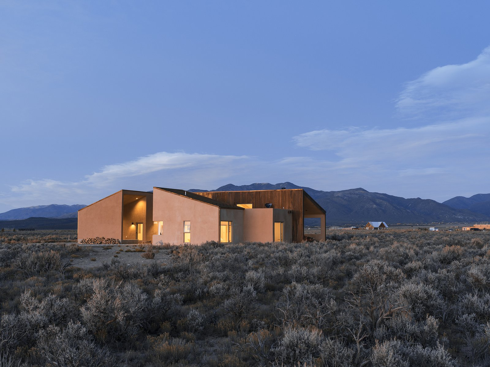 """Desert, Shrubs, Exterior, Stucco, House, and Wood On a five-acre property outside Taos, New Mexico, designer Molly Bell worked closely with her father, builder Ed Bell, to create a new residence for owner Lois Rodin. """"Lois requested that it appear as a grouping of individual masses, so that it read more like a cluster than a solitary shape,"""" Molly says. """"I hope it shows that it's OK to do something modern in such a traditional environment, and not to be afraid of it."""" - Taos, New Mexico Dwell Magazine : July / August 2017  Best Exterior Desert Photos from A Rookie Designer and Her Builder Father Create an Artist's Sculptural Loft in the Desert"""