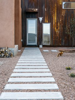 Rusted metal, used on three of the home's five roofs, extends to the entrance facade, which, in a nod to northern New Mexico's haciendas, opens to a courtyard. Rather than buy pre-rusted siding, Molly and her father oxidized the steel themselves. - Taos, New Mexico Dwell Magazine : July / August 2017