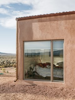 "A gravel perimeter keeps mud from splashing on the walls when it rains. Adds Molly, ""You can get away with minimal landscaping because there's so much natural vegetation here."" - Taos, New Mexico Dwell Magazine : July / August 2017"