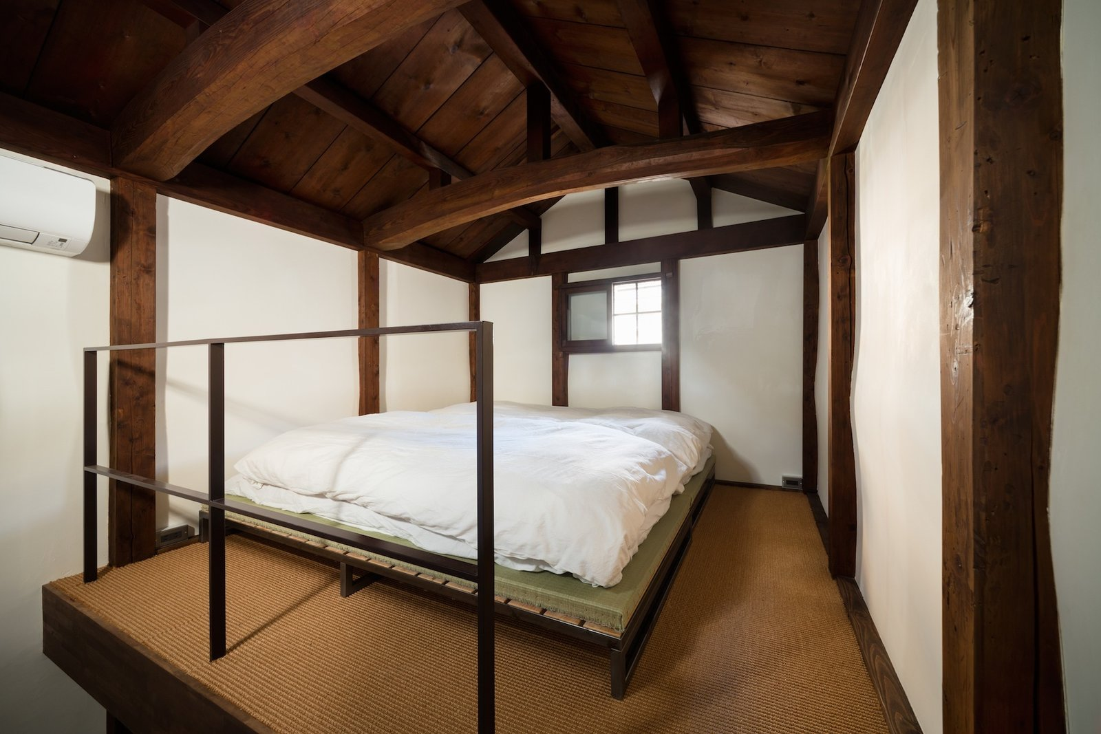 Bedroom, Bed, and Carpet Floor The second floor bedroom is surrounded by clay walls.  A tatami and futon provide sleeping quarters for two people; a mattress is available, too.  Photo 9 of 13 in A Minimalist Townhouse Provides Serene Accommodations in Historic Kyoto