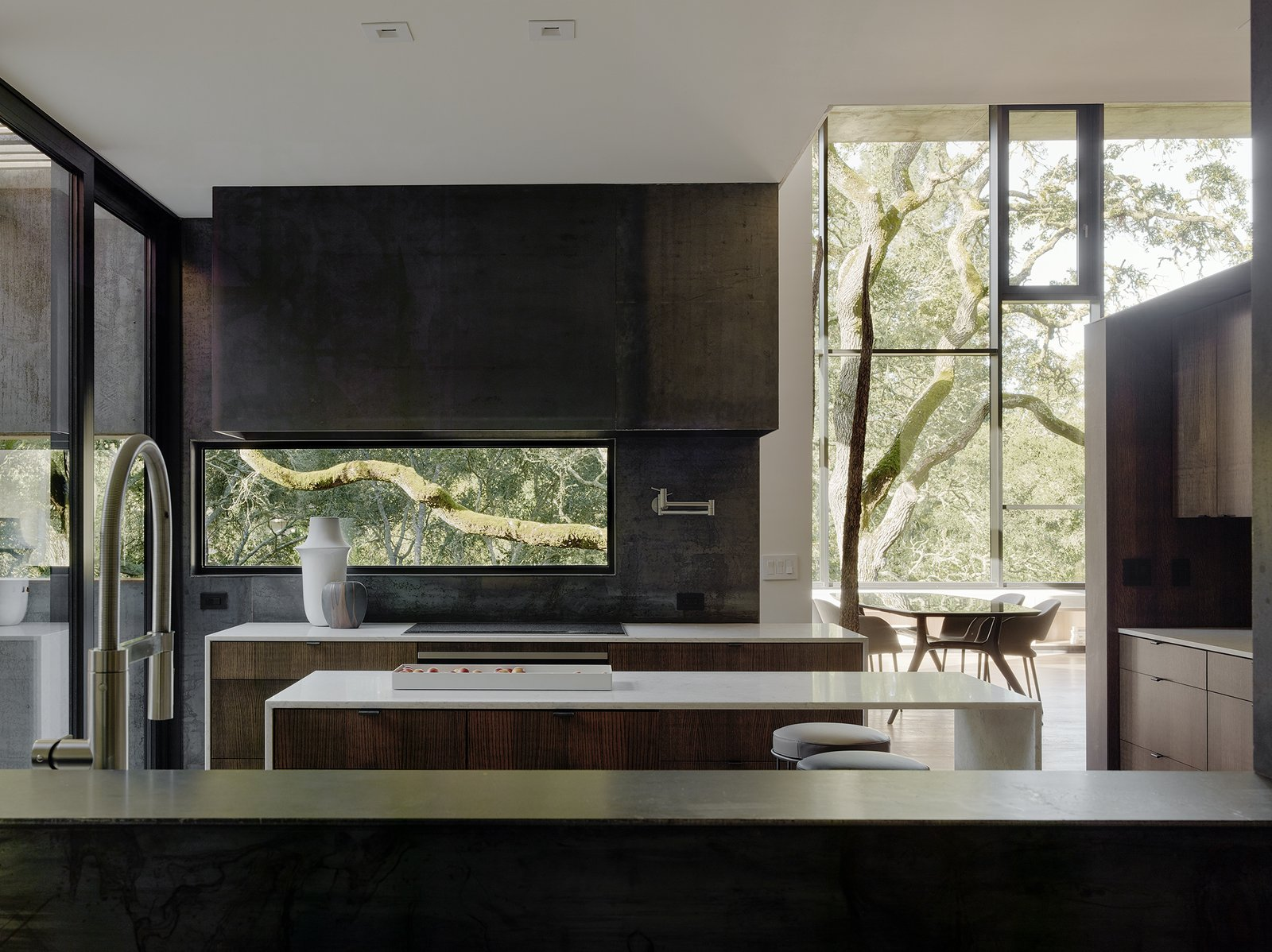 Kitchen, Wood Cabinet, Cooktops, Light Hardwood Floor, Metal Backsplashe, Recessed Lighting, and Metal Counter In the kitchen, bar stools by Living Divani pull up to an island with Bretonstone countertops; the faucet is by Blanco.  Photo 4 of 14 in Nature Drove the Design of This Sculptural, Cor-Ten Steel House in Northern California