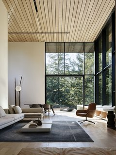 The living room features a sectional sofa and leather chair by Zanotta, coffee tables by Porro, a Kymo rug, and a floor lamp from Flos.