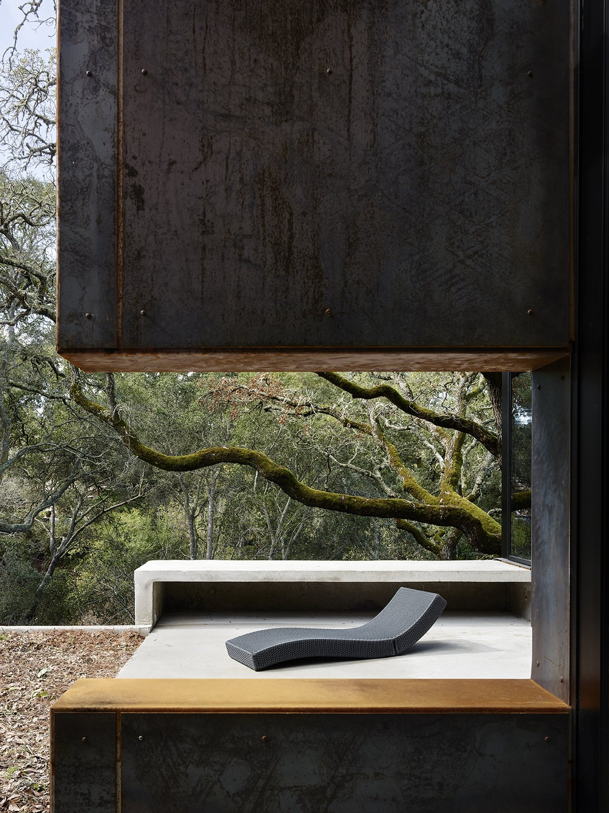Outdoor and Small Patio, Porch, Deck An opening in a Cor-Ten steel—clad wall on the terrace frames the Paola Lenti chaise longue.  Photo 13 of 14 in Nature Drove the Design of This Sculptural, Cor-Ten Steel House in Northern California