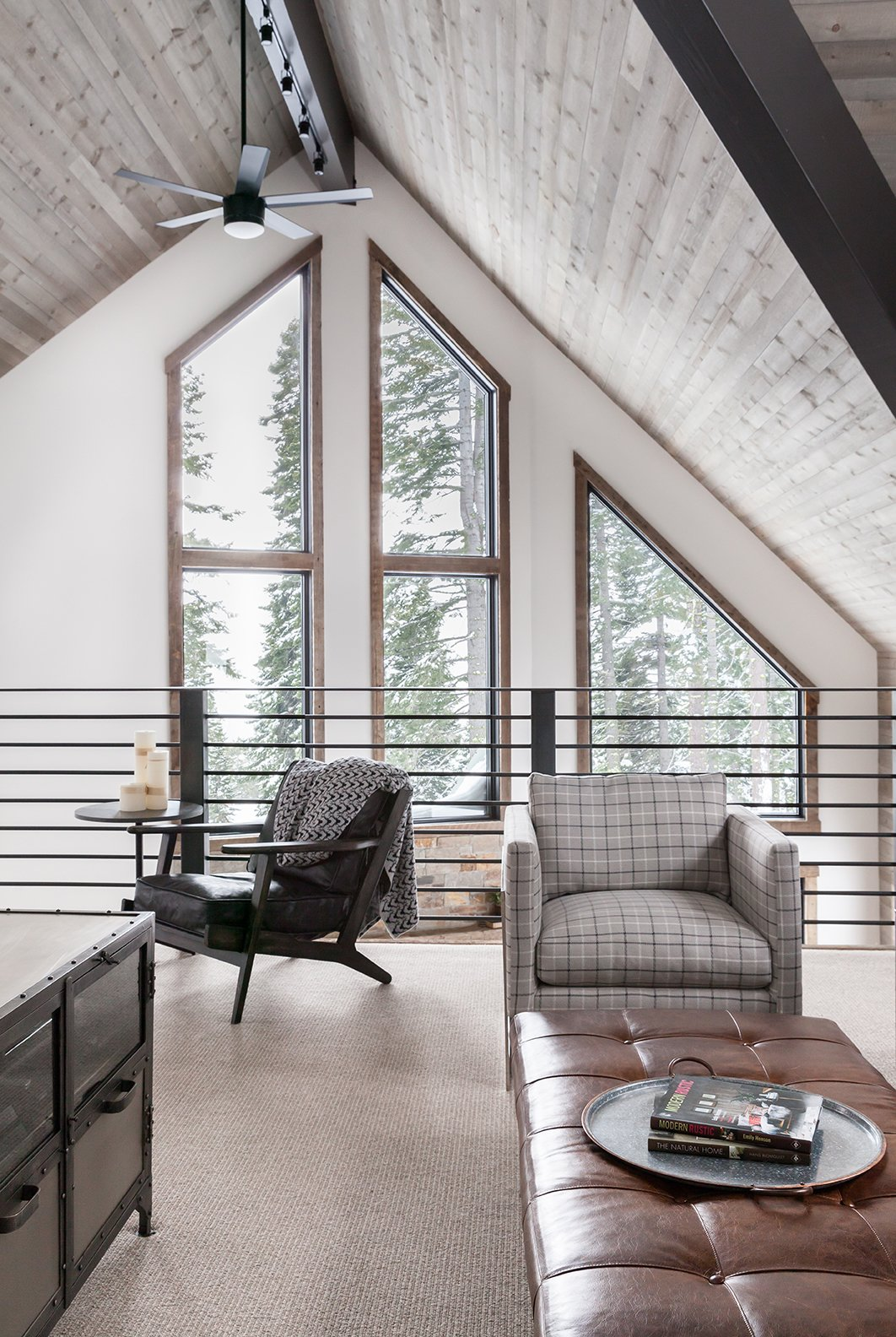 Living Room, Ottomans, Storage, Chair, End Tables, Carpet Floor, and Track Lighting  Dwell Magazine : September / October 2017  Photos from In This A-Frame Cabin Makeover, Simplicity Is Key